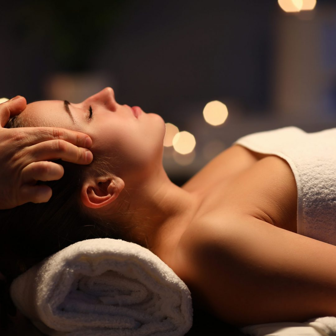 Woman lay on couch on her back with closed eyes and enjoy. Man make relaxing and therapeutic head massage at weight. Spa client has thrown her head back and rejuvenate. Wellness procedures in spa salon concept.